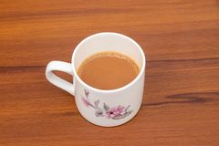 Cup of tea with milk isolated on wooden background stock photography