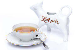 A cup of tea with a milk jug Stock Photos