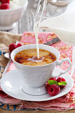 Cup of tea with milk pouring over Stock Images