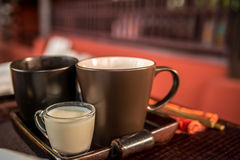 Cup of tea with milk at the wooden table Royalty Free Stock Photos