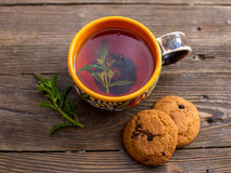Cup of tea with mint and cakes. Teatime - relax with hot black tea. Aromatic black tea brewed in cup. A cup of black tea with mint on a wooden surface Royalty Free Stock Photography