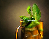 Cup of tea with mint. Close-up cup of tea with mint and ice on toned brown background stock photos