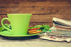 Cup of tea, mint, cookie, bunch of newspapers and magazines Stock Photo