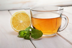 Cup of tea. Mint and lemon on a wooden table Royalty Free Stock Photography