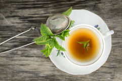 Cup of tea with mint and tea strainer on old wooden table Stock Image