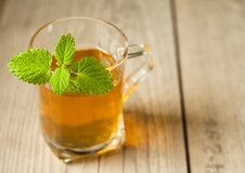 Cup of tea with mint on wooden table Royalty Free Stock Photos