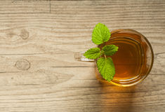 Cup of tea with mint on wooden table Royalty Free Stock Image