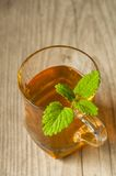 Cup of tea with mint on wooden table Royalty Free Stock Photo