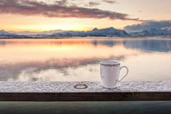 A cup of tea with a beautiful scenery in the background. A cup of tea in the morning with a beautiful scenery in the background royalty free stock images