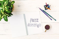 Cup of tea in morning and text in Notepad: Felize Domingo. Happy Sunday In Spanish Stock Image
