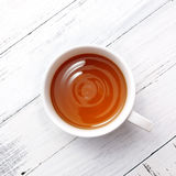 Cup of tea with moving of the water. On white wooden background Stock Photos