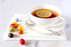 Cup of tea and multicolored chocolate drops Royalty Free Stock Image