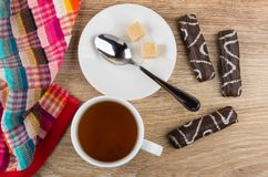 Cup of tea, napkin, sugar, teaspoon, marshmallow in chocolate. On wooden table. Top view Stock Images