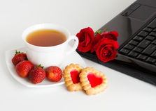 Cup of tea is near computer. Cup of tea standing near a laptop Stock Image