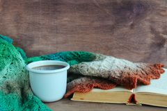 A cup of tea near the rustic handmade knitted warm autumn or winter scarf brown, orange, white, grn and grey colors on wooden back royalty free stock photo