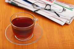A cup of tea next to the newspaper. Royalty Free Stock Photo