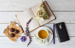 A cup of tea, a note book, several candies, a necklace nad flowers. A photo representing a spring women inspiration: a cup of tea, a note book, several candies stock photos