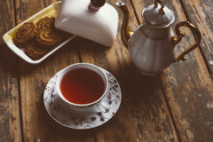 Cup of tea. O old wood board with some cookies and teapot Royalty Free Stock Images
