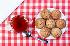 Cup of tea, oatmeal cookies, white napkin on a red white tablecl Stock Photos