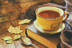 Cup of tea with old book. Autumn leaves and a warm scarf on wooden table Stock Photography