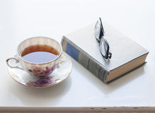 Cup of tea, old book and glasses Stock Photography