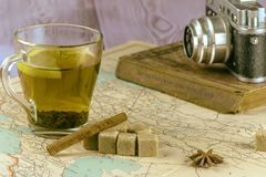 A Cup of tea is on the old map. The old retro camera lies on a shabby book. royalty free stock photography