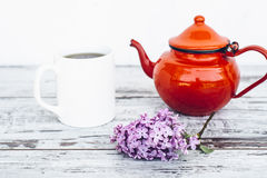 Cup of tea and old red teapot on vintage wooden table with branch of lilac Stock Photo