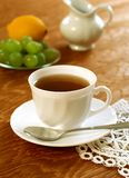 Cup of tea on old wooden. White cup of tea and fruit on old wooden Royalty Free Stock Photography