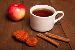 Cup of tea on old wooden table with  apple, dried apricots and c Royalty Free Stock Image