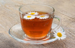 Cup of tea on old wooden table with flowers of camomile Royalty Free Stock Photos