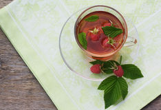 Cup of tea on old wooden table with raspberry and leaves. Cup of tea on a saucer from transparent glass on a green cloth on an old wooden table with raspberry Royalty Free Stock Image
