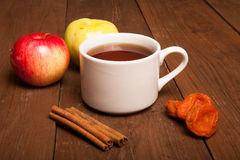 Cup of tea on old wooden table with two apples, dried apricots a Royalty Free Stock Photos