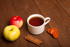Cup of tea on old wooden table with two apples, dried apricots a Stock Images