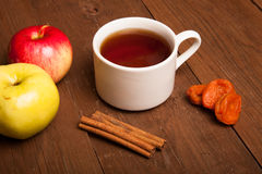 Cup of tea on old wooden table with two apples, dried apricots a Stock Photo