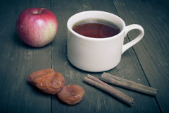 Cup of tea on old wooden table with two apples, dried apricots a Royalty Free Stock Image