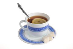 A cup of tea with one slice of lemon within and refined sugar on Royalty Free Stock Photography