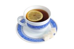 A cup of tea with one slice of lemon within and refined sugar on Royalty Free Stock Photos