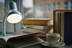 A cup of tea, open book under the lamp Stock Photo