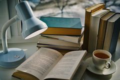 A cup of tea, open book under the lamp. On the window Royalty Free Stock Image