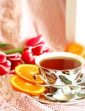 Cup of tea, orange and tulips royalty free stock photography