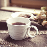 Cup of tea on ornamented table cloth Stock Photos