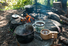 A cup of tea outdoors. A campfire with an outdoor cookware with freshly boiled tea Stock Photography