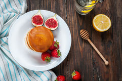 Cup of tea and pancakes with figs, strawberries on white plate closeup Royalty Free Stock Photo