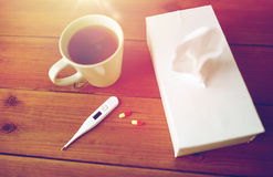 Cup of tea, paper wipes and thermometer with pills Royalty Free Stock Photo