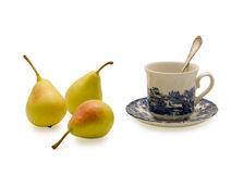 Cup for tea and pears. Porcelain cup with a plateau and the small spoon for tea, also three yellow pears Stock Photography