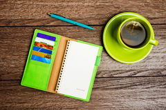 Cup of tea, pen, opened organizer. On the wooden table Stock Images