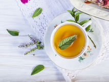 Cup of tea with peppermint on white wooden table Stock Images