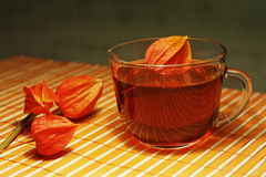 Cup of tea and physalis on a bamboo table cloth Royalty Free Stock Photography