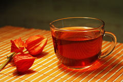 Cup of tea and physalis on a bamboo table cloth Stock Photography