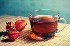 Cup of tea and physalis on a bamboo table cloth Royalty Free Stock Photo